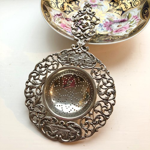 A Dutch Silver Tea Strainer With Country Scenes.