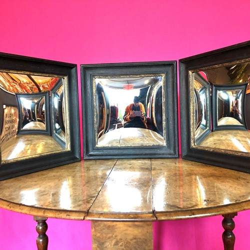A set of wooden ebonised convex distortion mirrors